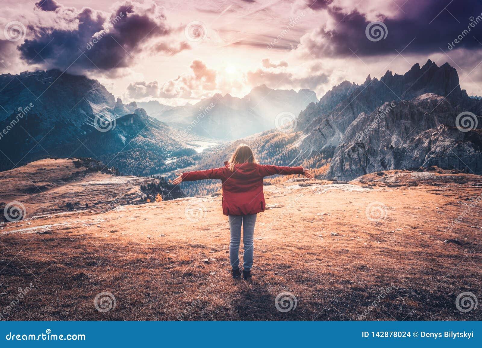 Ung kvinna med lyftta upp armar och berg på solnedgången