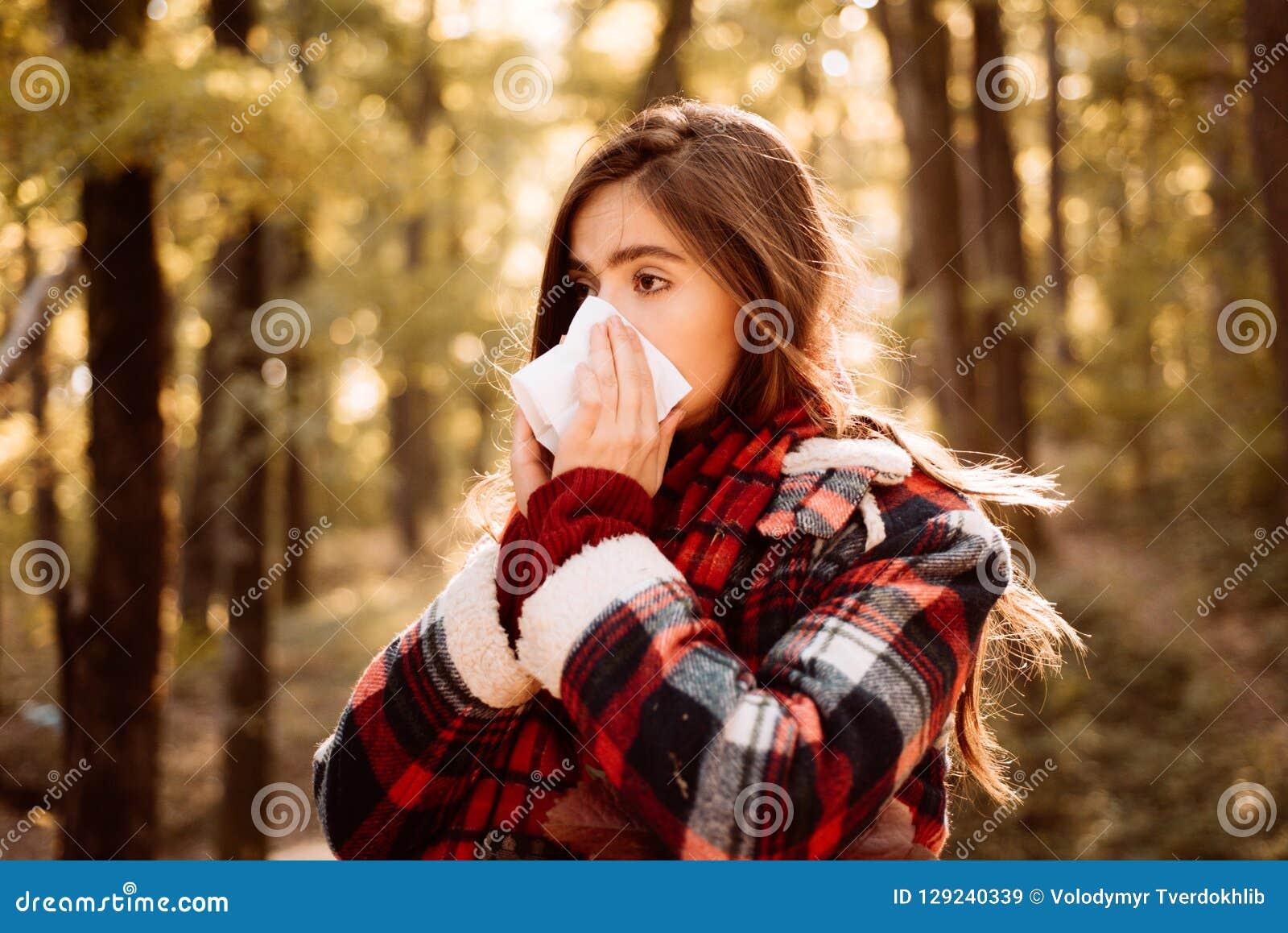 Ung kvinna med nästorkaren nära höstträd Sjuk flicka med den rinnande näsan och feber Uppvisning av den sjuka kvinnan som nyser p