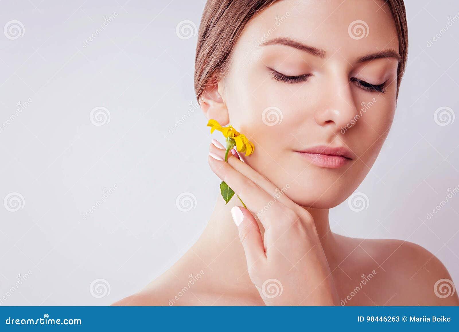 Ung kvinna med naturlig makeup som rymmer en blomma Organiskt skönhetsmedelbegrepp