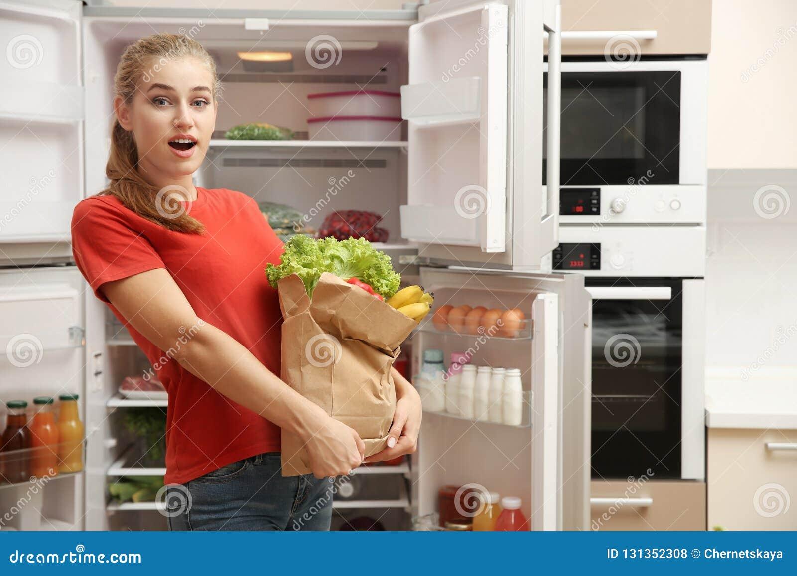 Ung kvinna med ny mat i pappers- påse nära kylskåpet