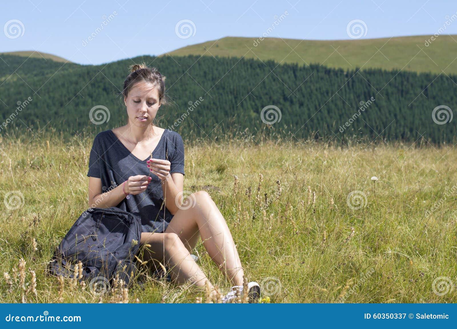 Ung kvinna med ryggsäcksammanträde i fältet och golding av en st