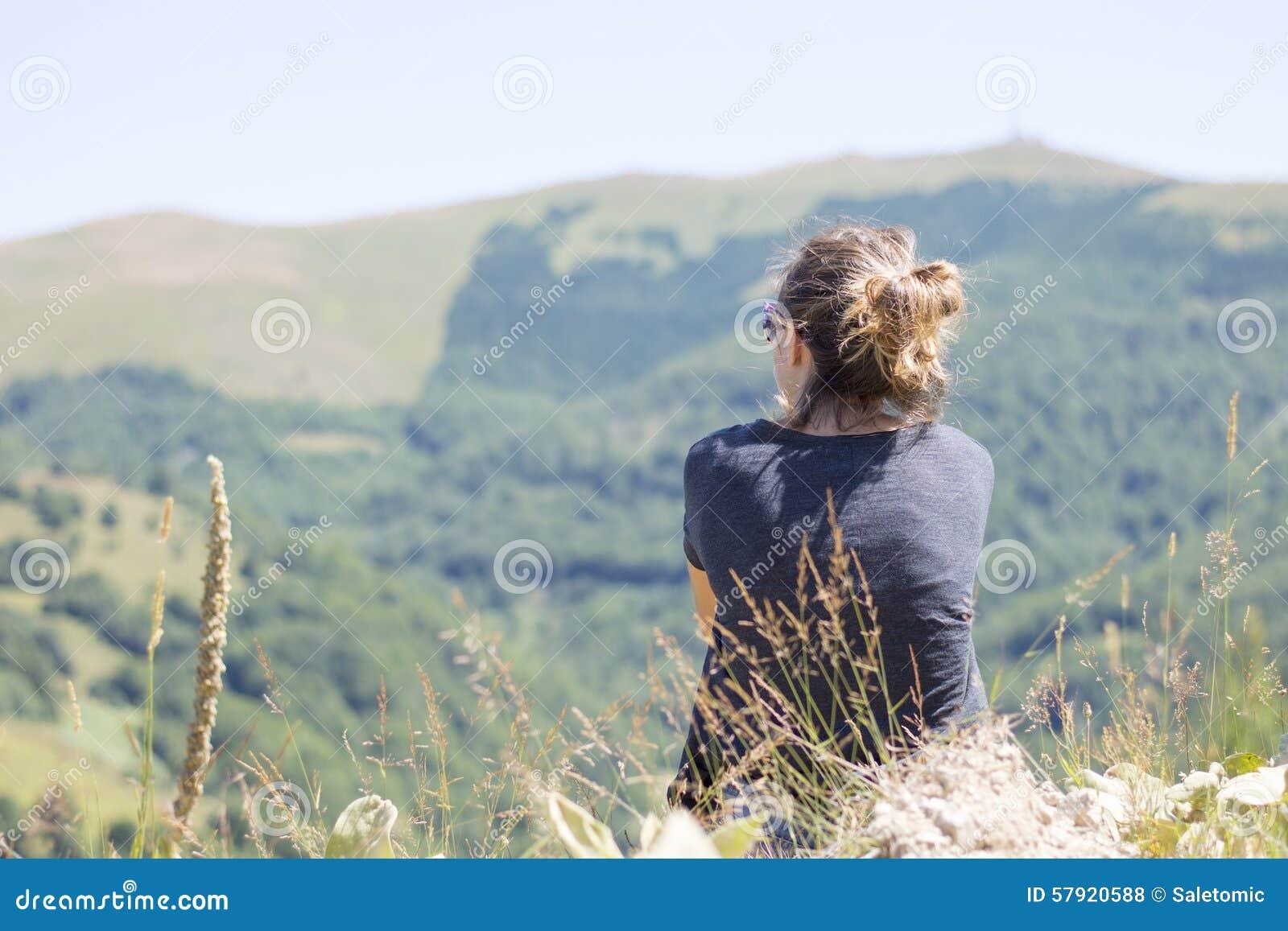 Ung kvinna med ryggsäcksammanträde på klippas kant och att se till