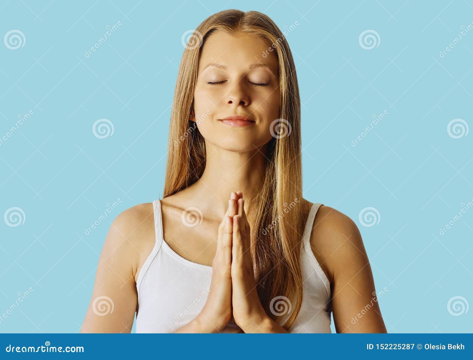 Ung kvinna med stängda ögon och händer, i att be gest Meditation, jämvikt och fred av meningsbegreppet ?ver bl?tt