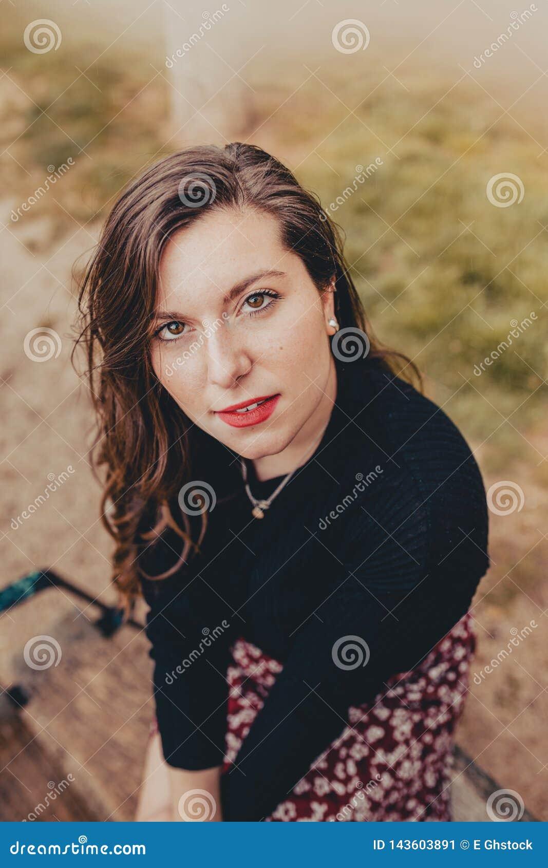 Ung kvinna med vått hår för regn som framåt ser rakt