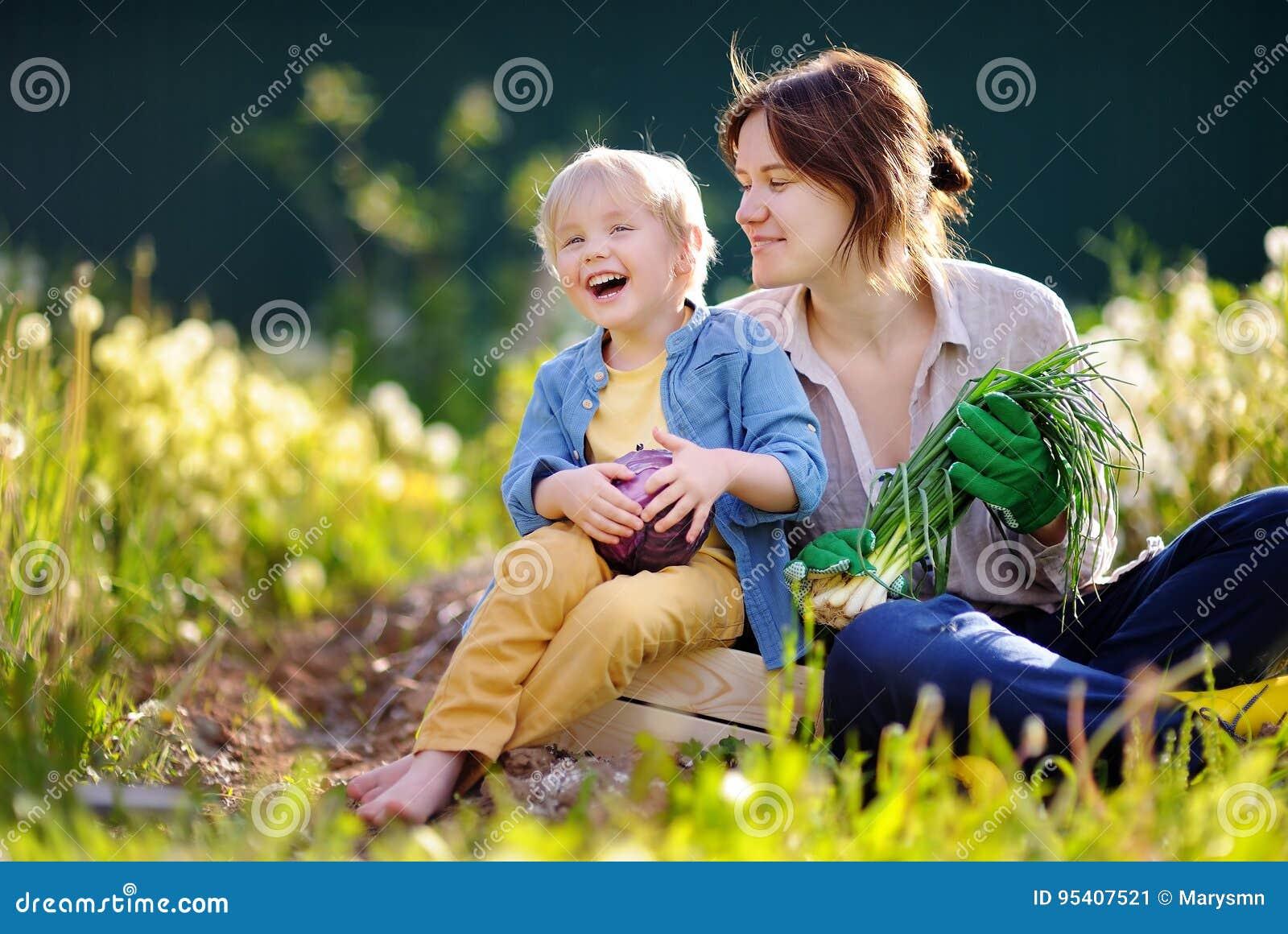 Ung kvinna och hennes förtjusande liten son som tycker om skörden