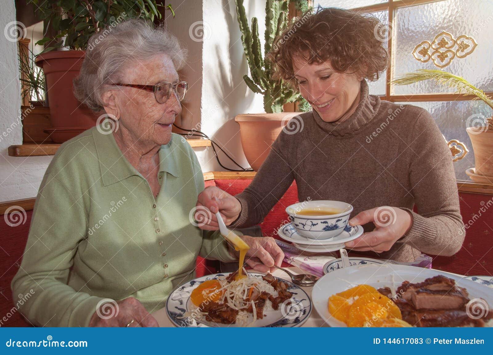 Ung kvinna och hennes lycklig farmor som har lunch på restaurangen