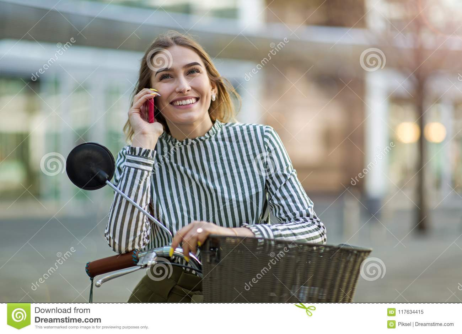 Ung kvinna på cykeln genom att använda mobiltelefonen