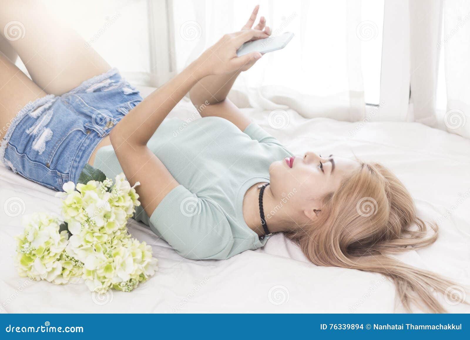Ung kvinna på sängbruksmobiltelefonen