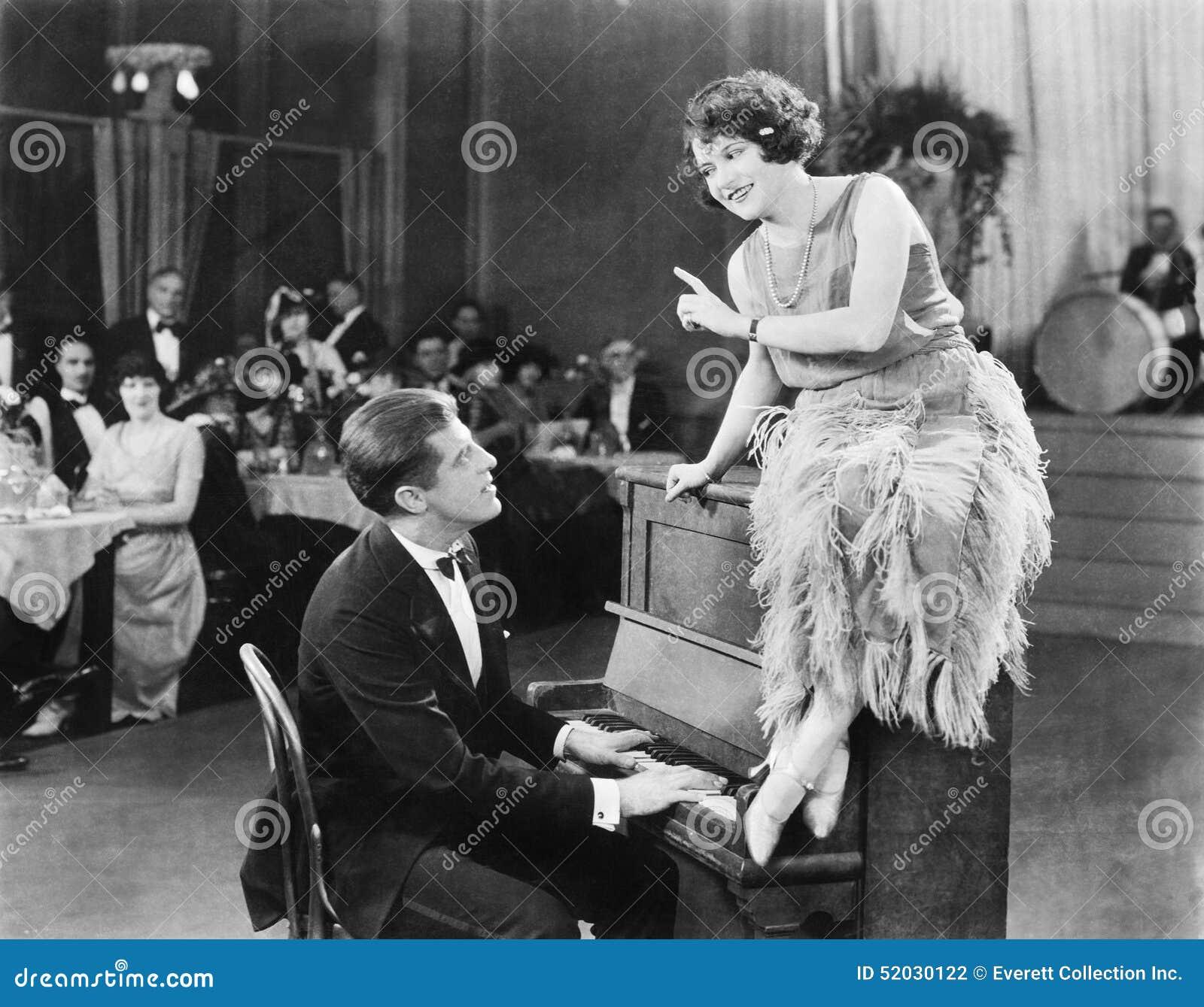 Ung kvinna sitta överst pianot och tala med pianisten (alla visade personer inte är längre uppehälle och ingen godsexi