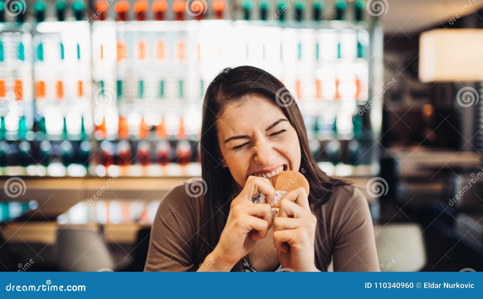 Ung kvinna som äter den fettiga hamburgaren Begärsnabbmat Tycka om skyldigt nöje som äter skräpmat Tillfredsställt uttryck avbrot