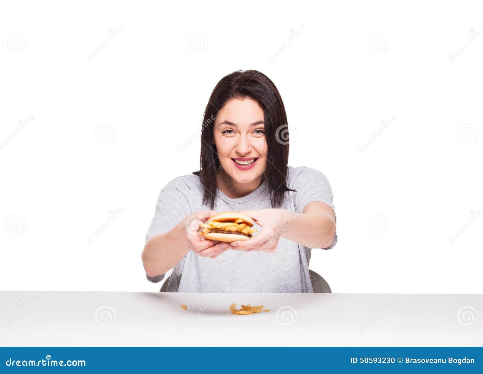 Ung kvinna som äter hamburgaren som isoleras på vit