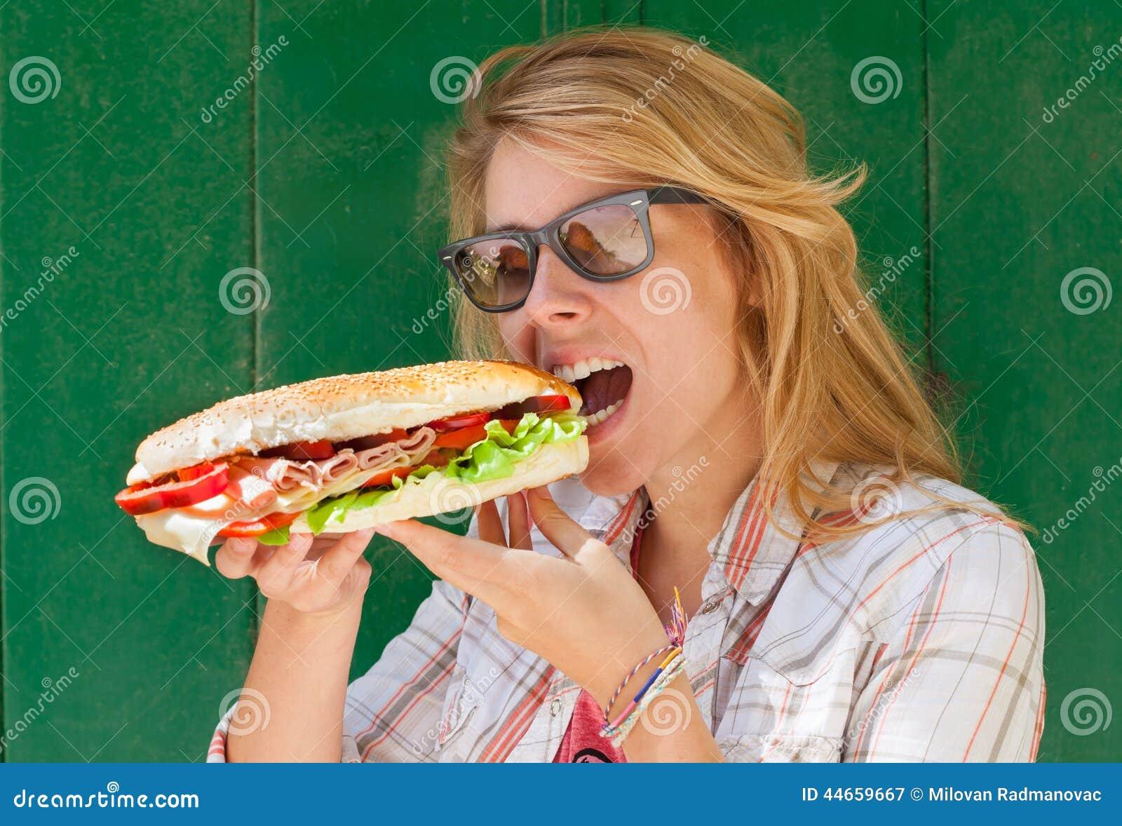 Ung kvinna som äter smörgåsen