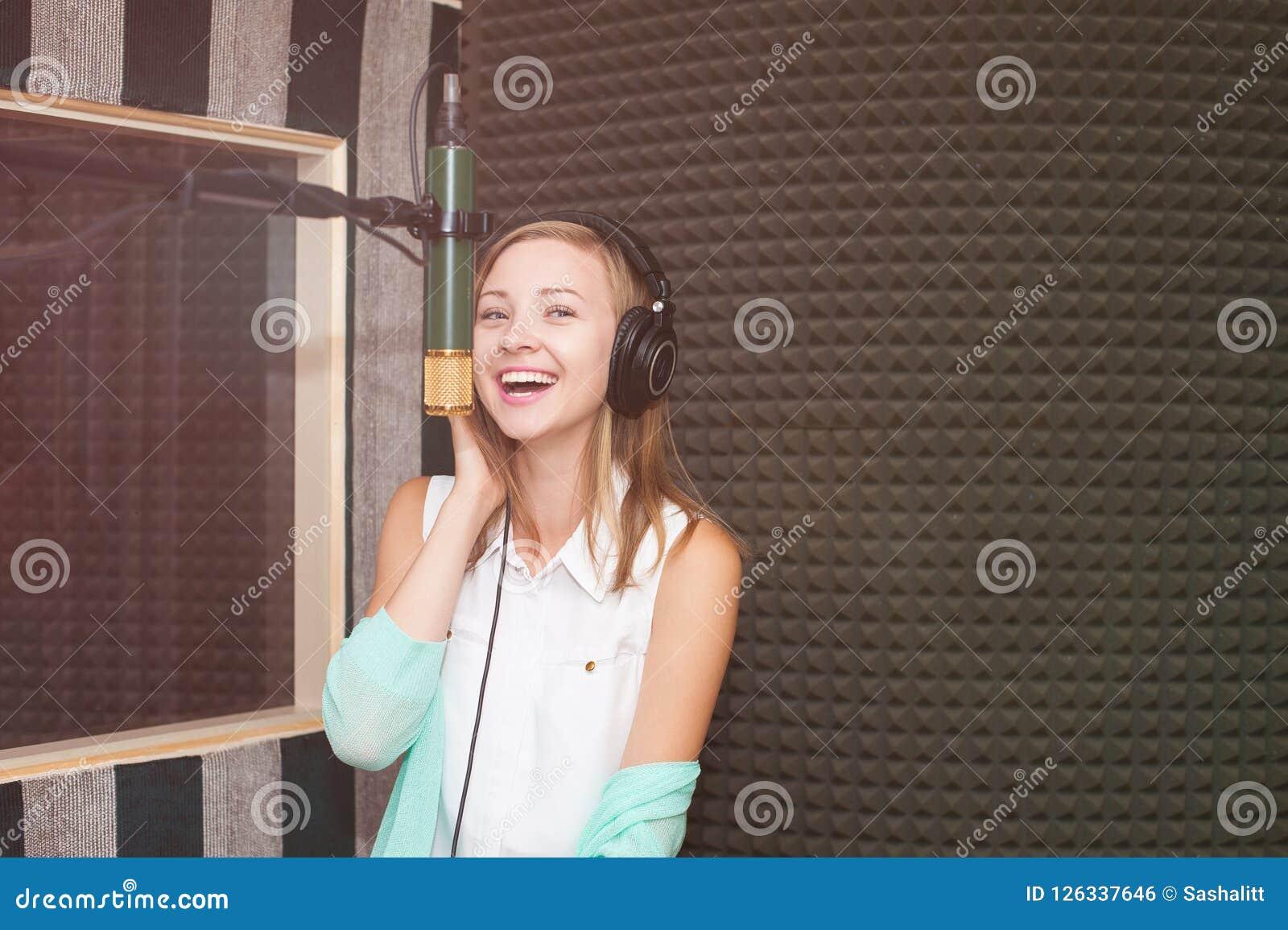 Ung kvinna som antecknar en sång i en yrkesmässig musikstudio