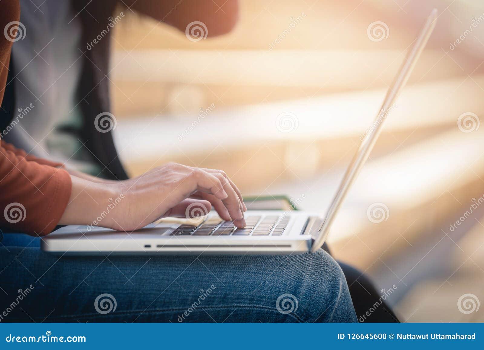 Ung kvinna som använder bärbar datordatoren på det utvändiga kontoret
