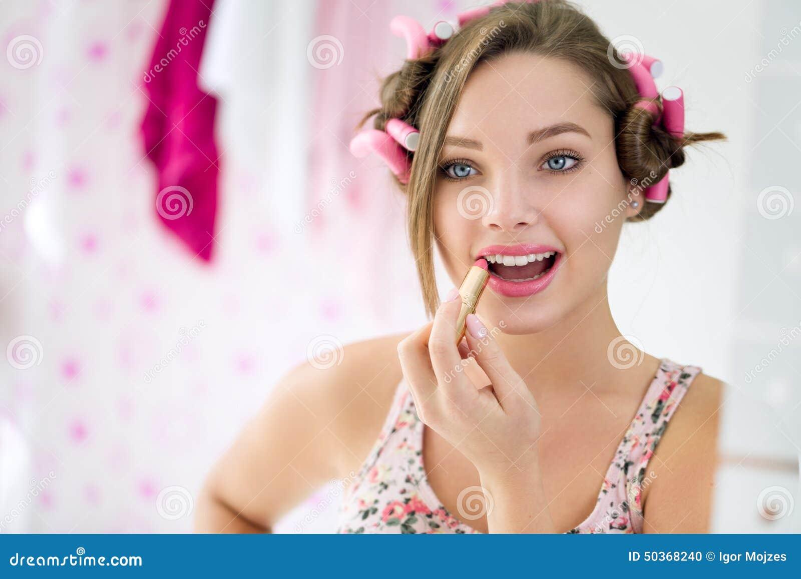 Ung kvinna som applicerar läppstift i badrum