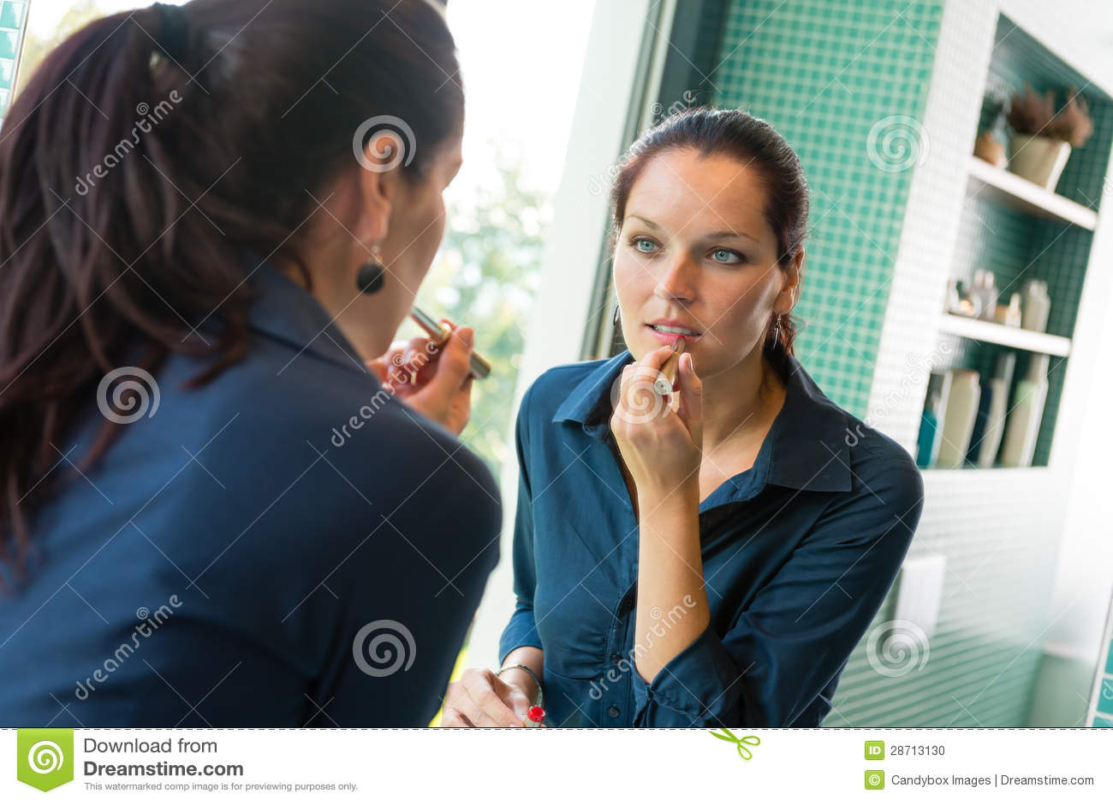 Ung kvinna som applicerar läppstiftsminkbadrummen