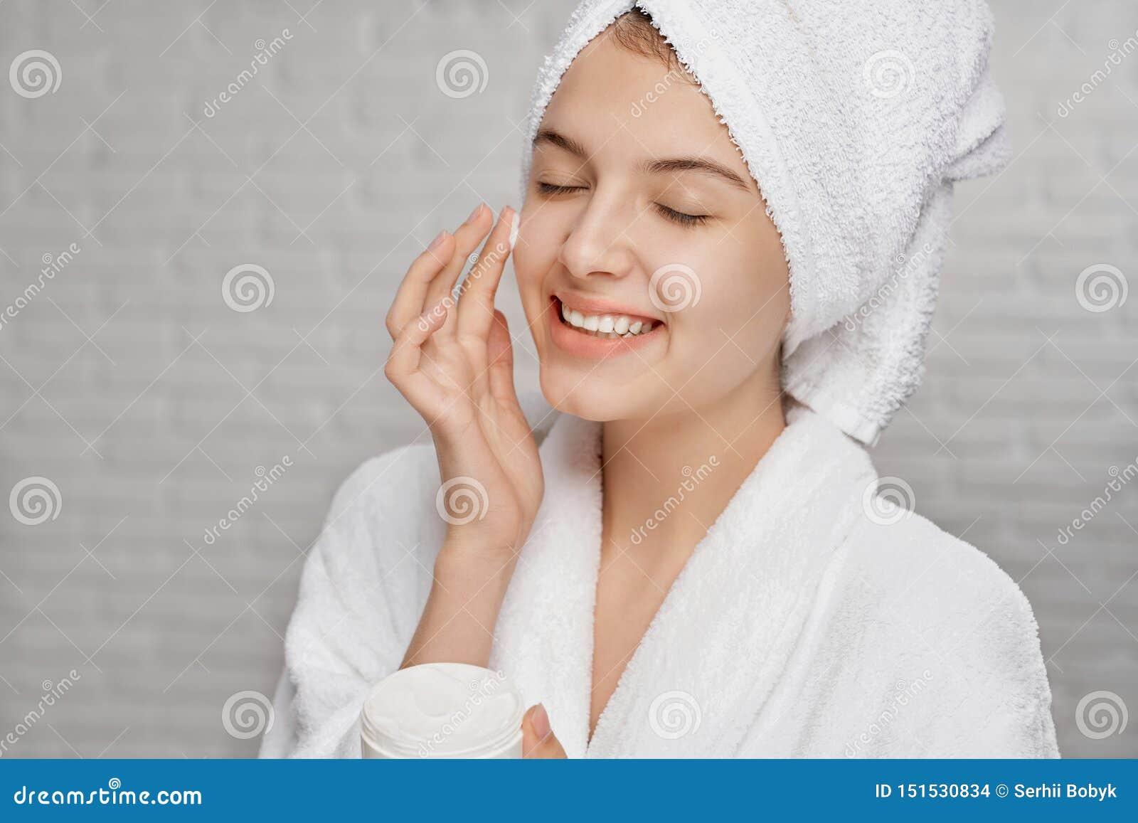 Ung kvinna som applicerar på framsidakräm för att hydratisera av hud