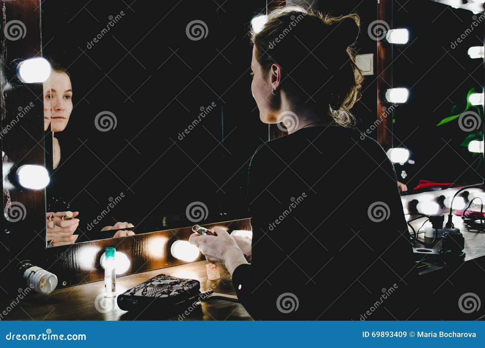 Ung kvinna som applicerar sminket som ser sig reflexion i spegel med kulor på dressingen i mörkt inre rum Flicka som applicerar c