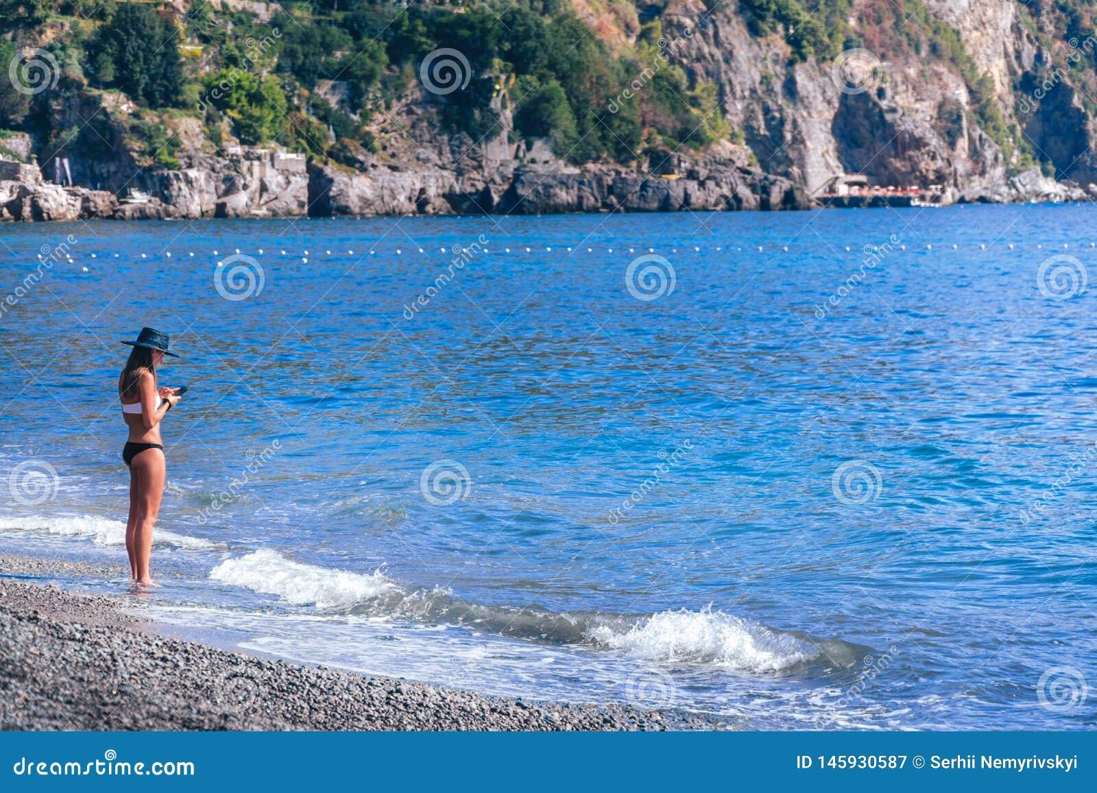 Ung kvinna som bara står på stranden och blicken på hennes telefon Bra begrepp, dålig signal