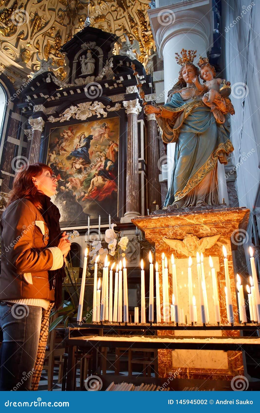 Ung kvinna som ber i en kyrka