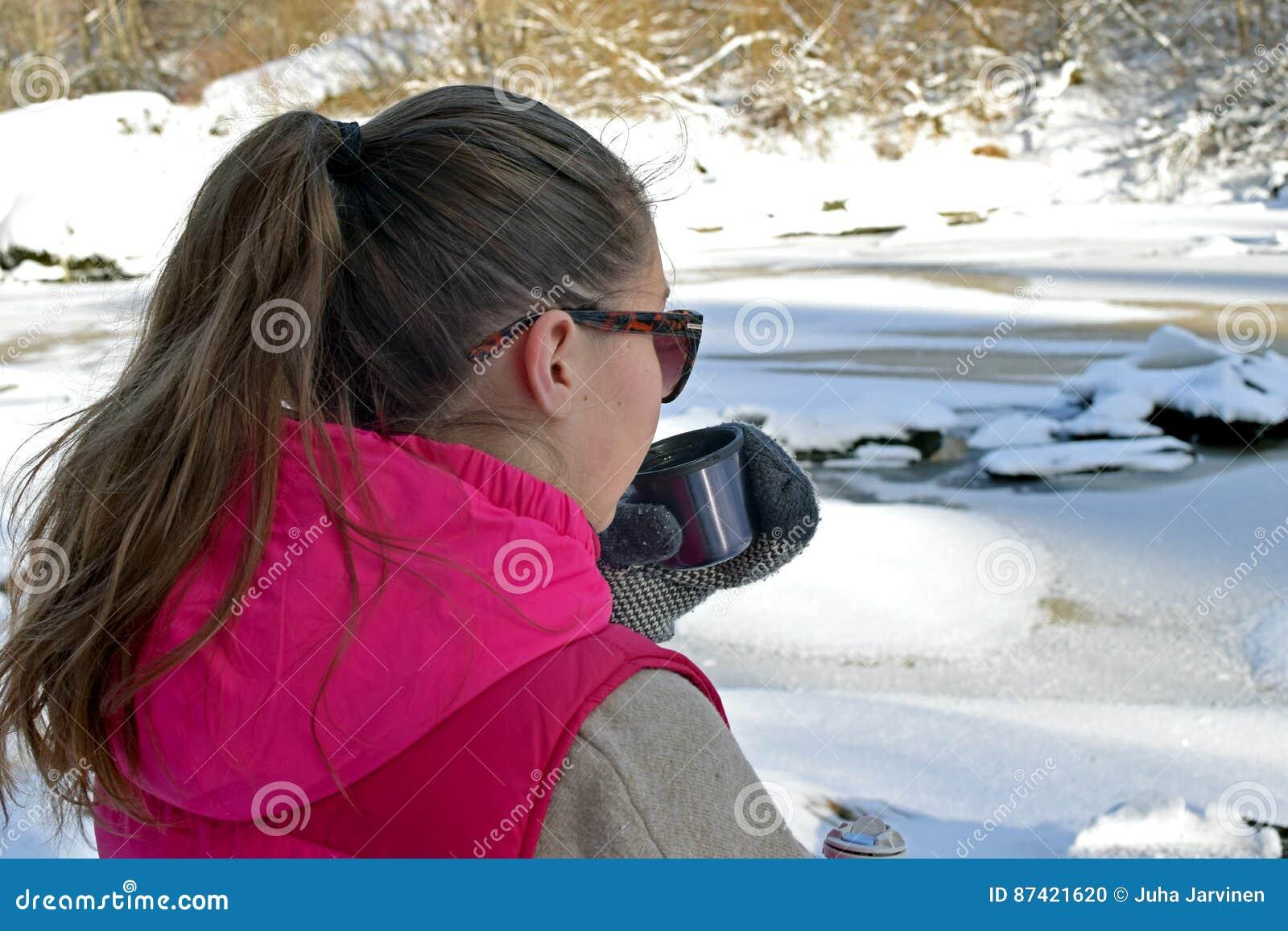 Ung kvinna som dricker varmt te på vinterskog