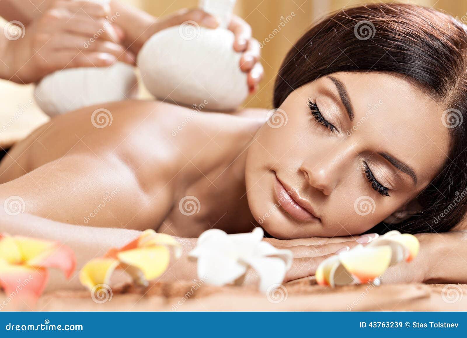Ung kvinna som får massage i brunnsortsalong