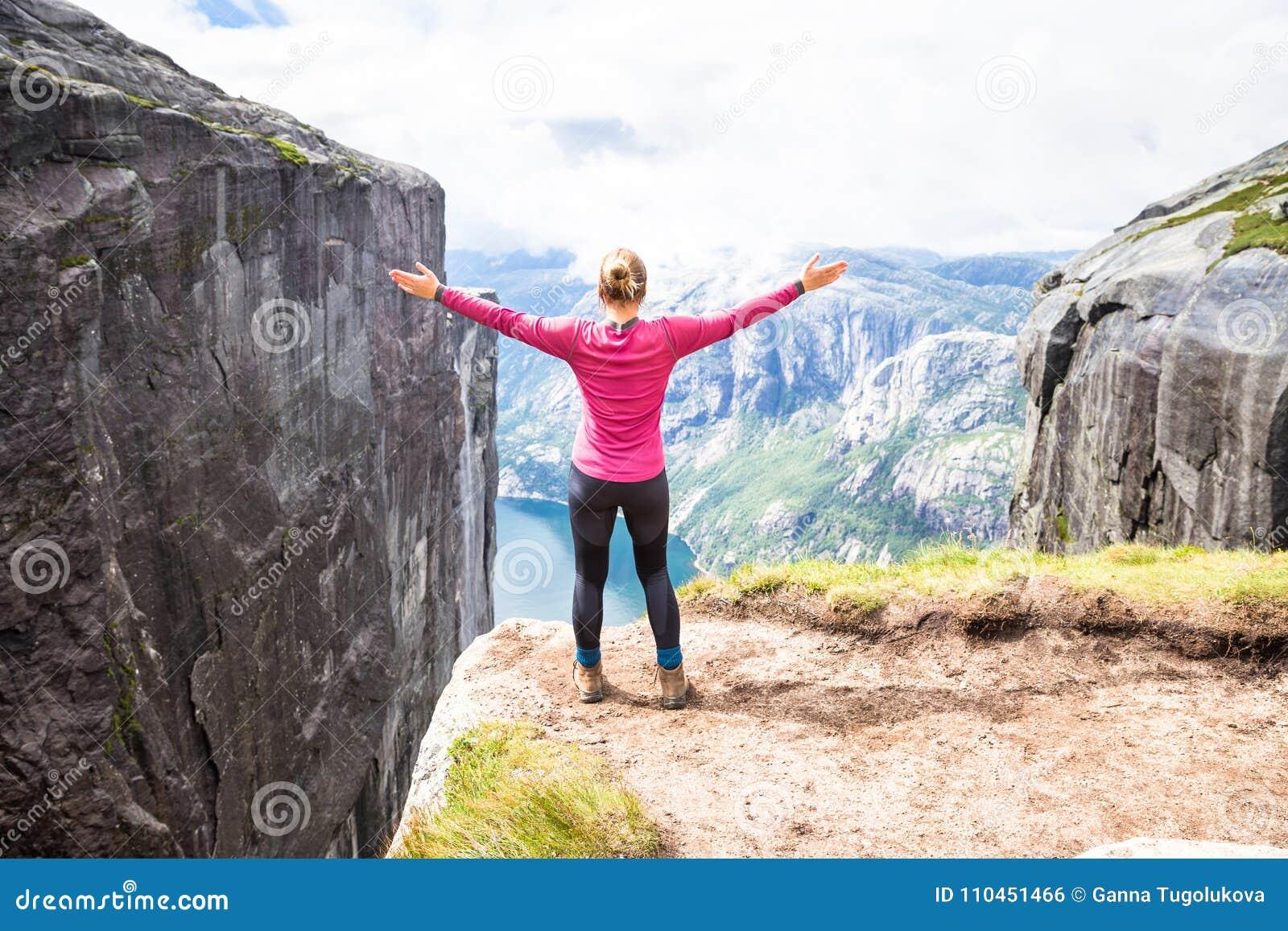 Ung kvinna som fotvandrar på kjerag Den lyckliga flickan tycker om den härliga sjön och bra väder i Norge