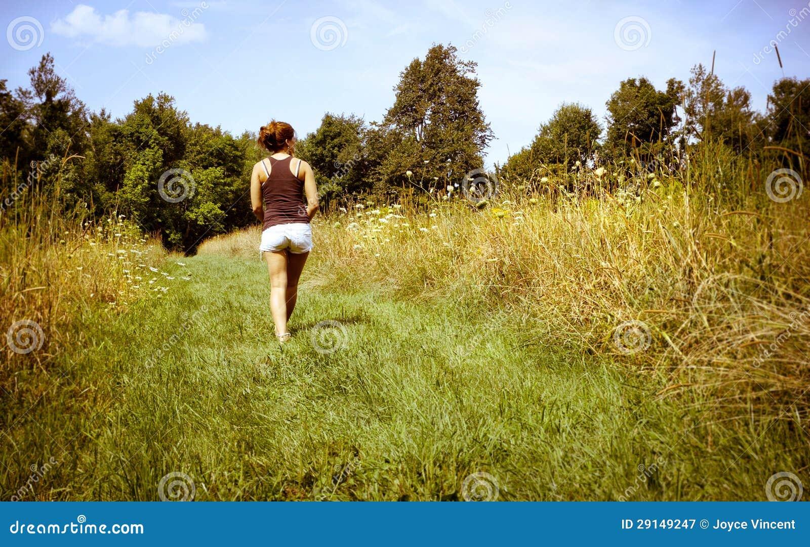 Ung kvinna som går bort i natur