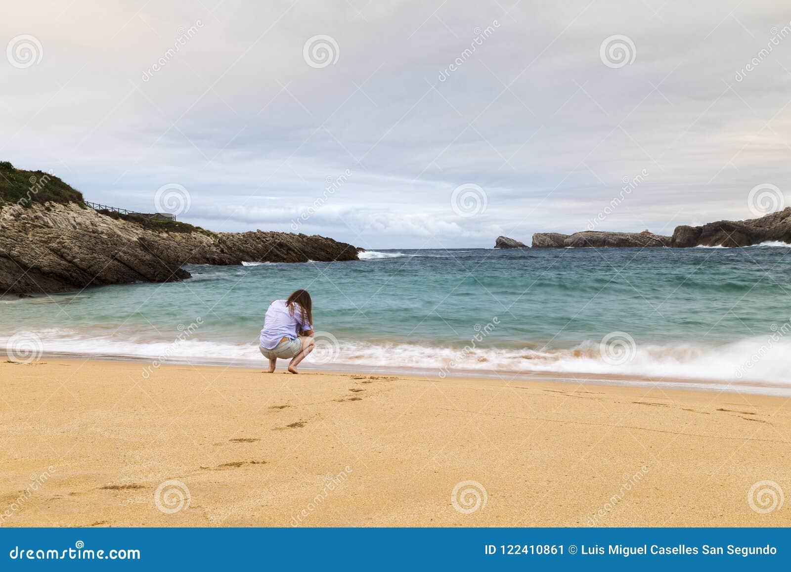 Ung kvinna som går på sanden av en härlig strand