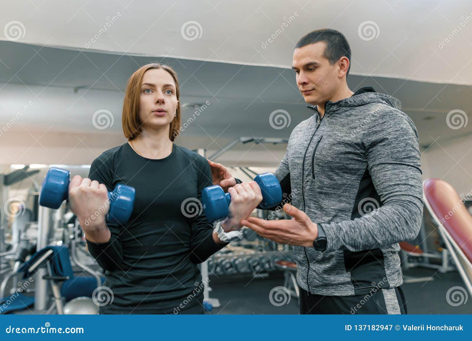 Ung kvinna som gör övningar med den personliga instruktören i idrottshall Sport, idrottsman nen, utbildning, sund livsstil och fo