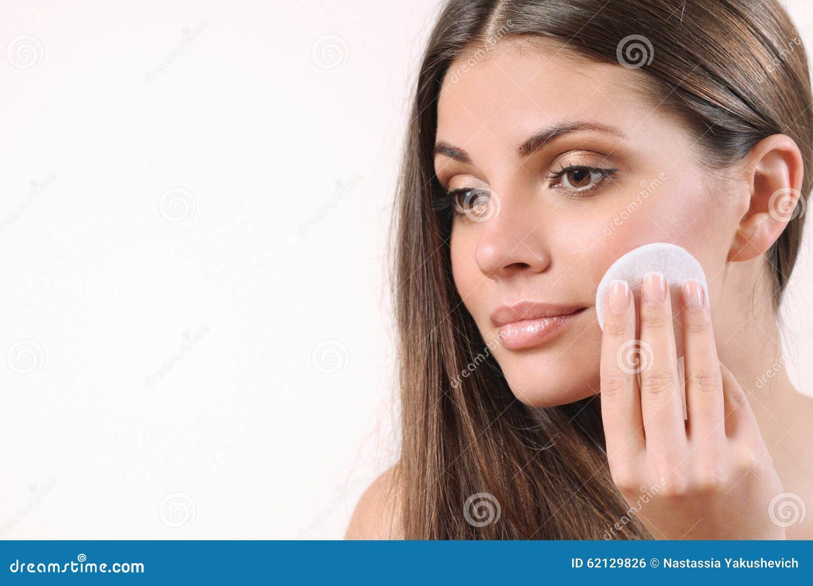 Ung kvinna som gör ren hennes hud på vit bakgrund