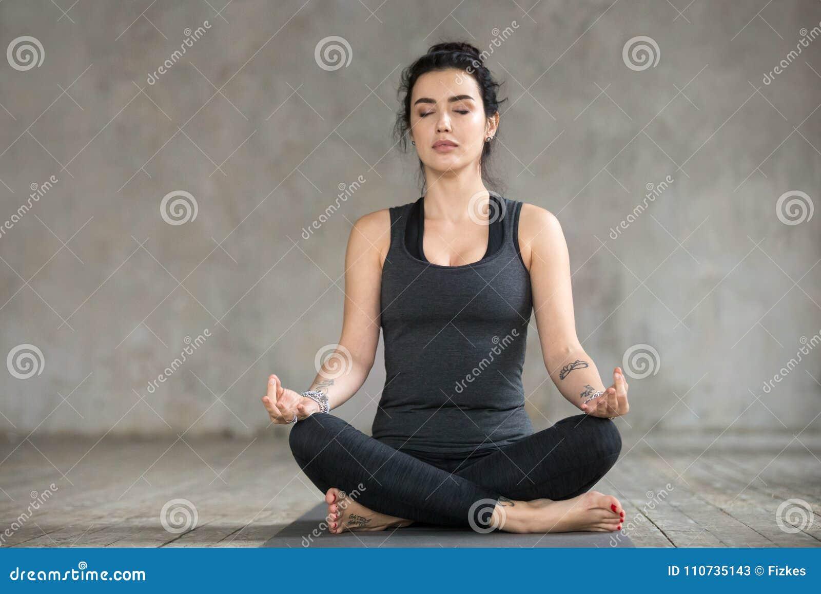 Ung kvinna som gör upp den Sukhasana övningen, slut
