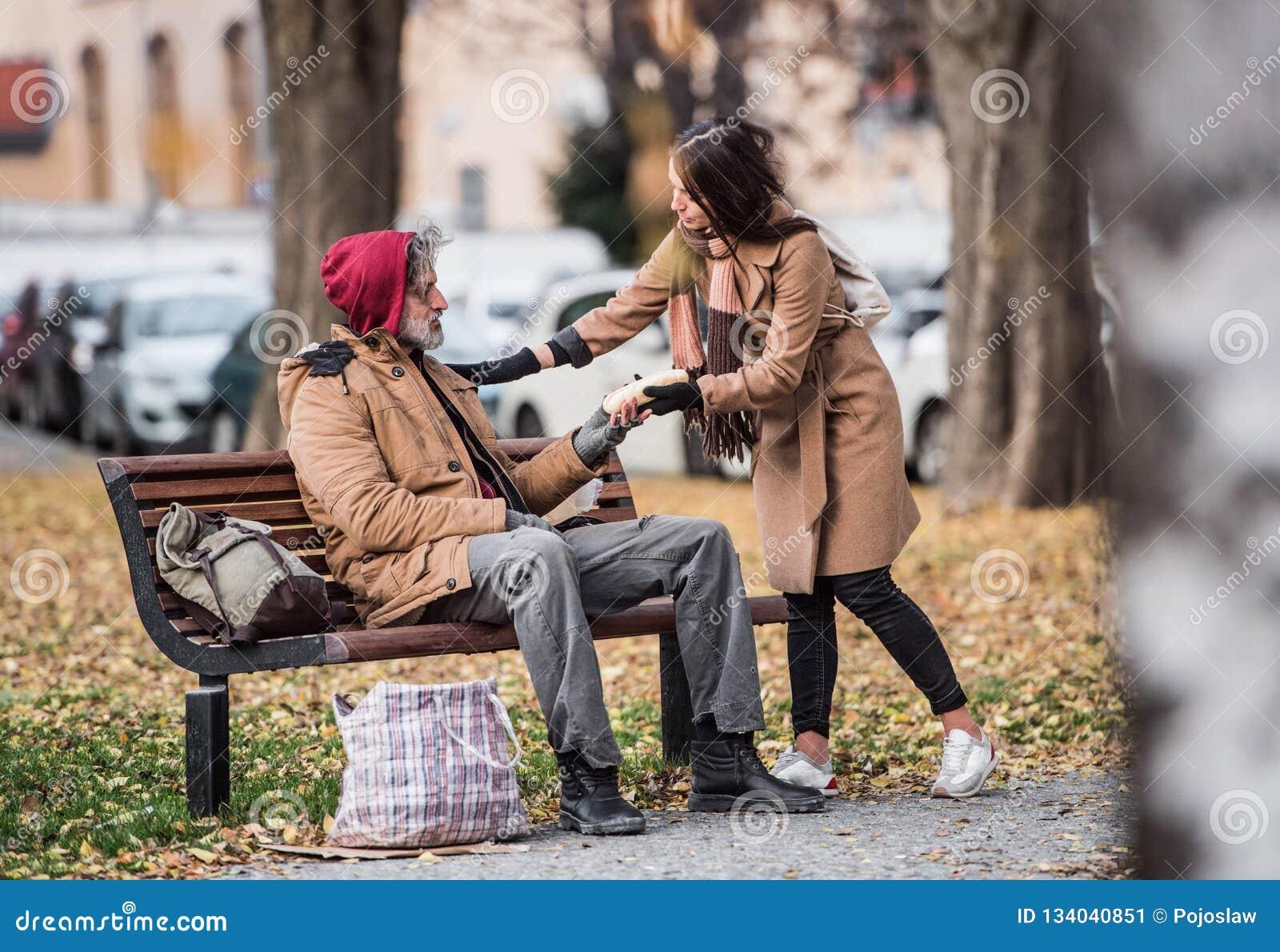 Ung kvinna som ger mat till den hemlösa tiggaremannen som sitter på en bänk i stad