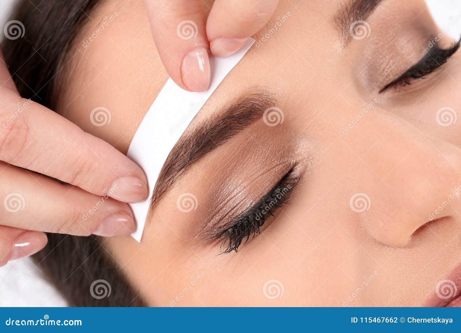 Ung kvinna som har det yrkesmässiga ögonbrynet