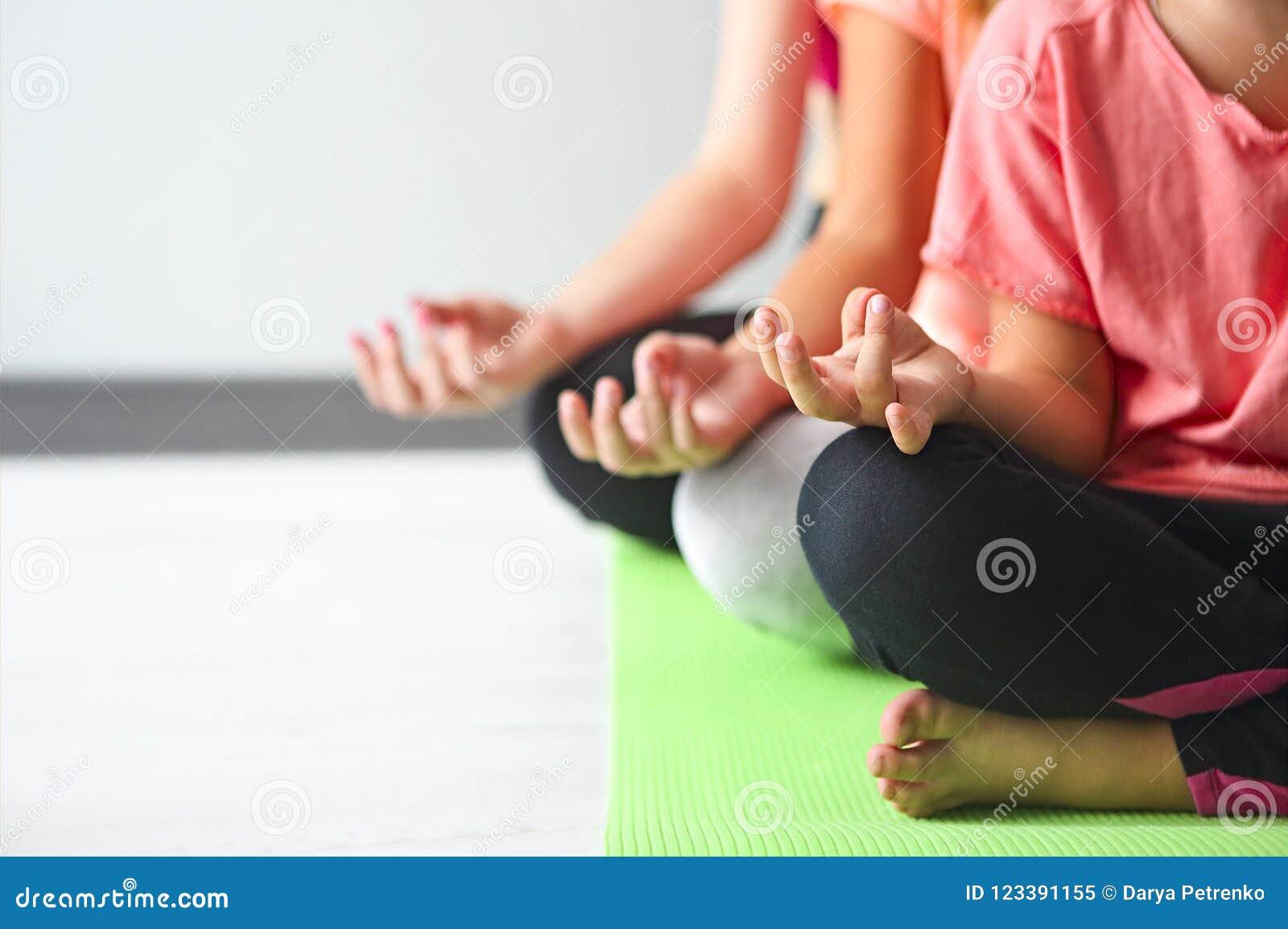Ung kvinna som har gyckel med ungar som gör yoga Familjsportconcep
