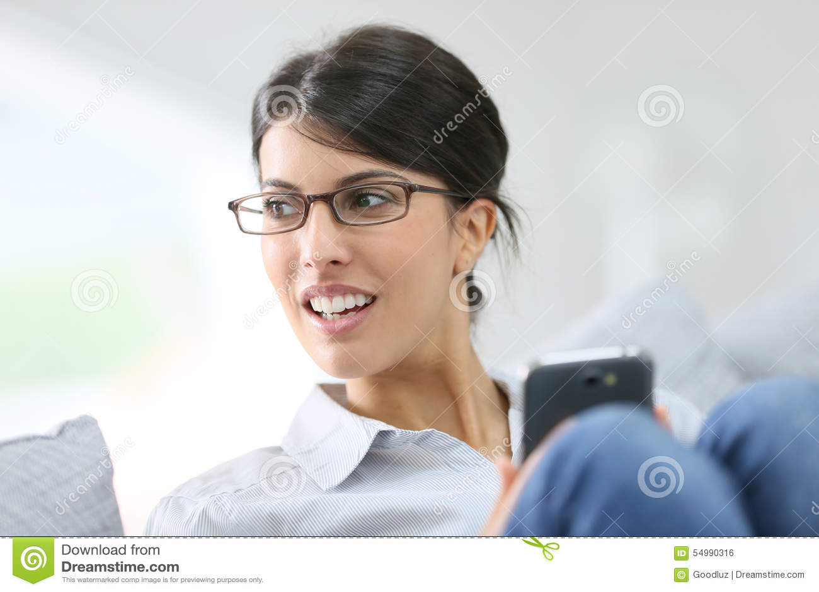 Ung kvinna som hemma använder smartphonen