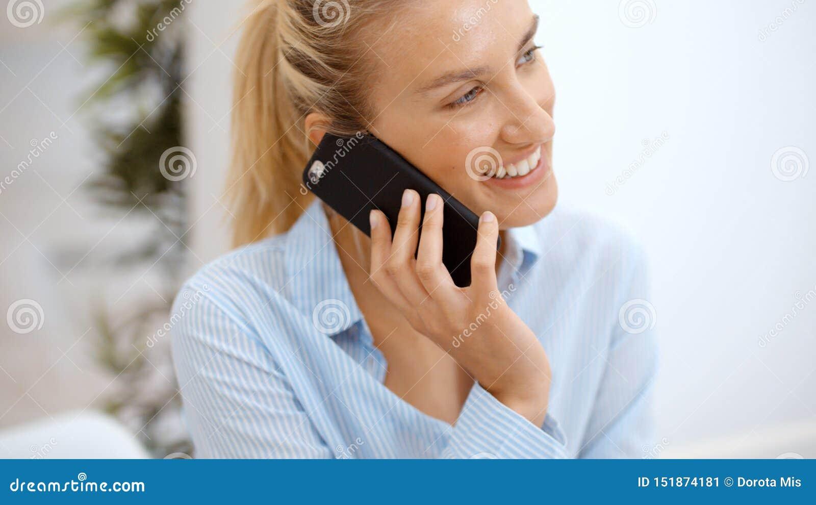 Ung kvinna som hemma anv?nder smartphonen