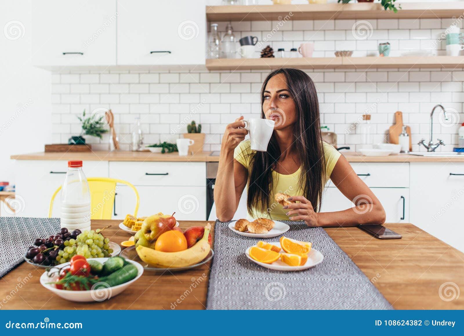 Ung kvinna som hemma dricker kaffe i morgonen