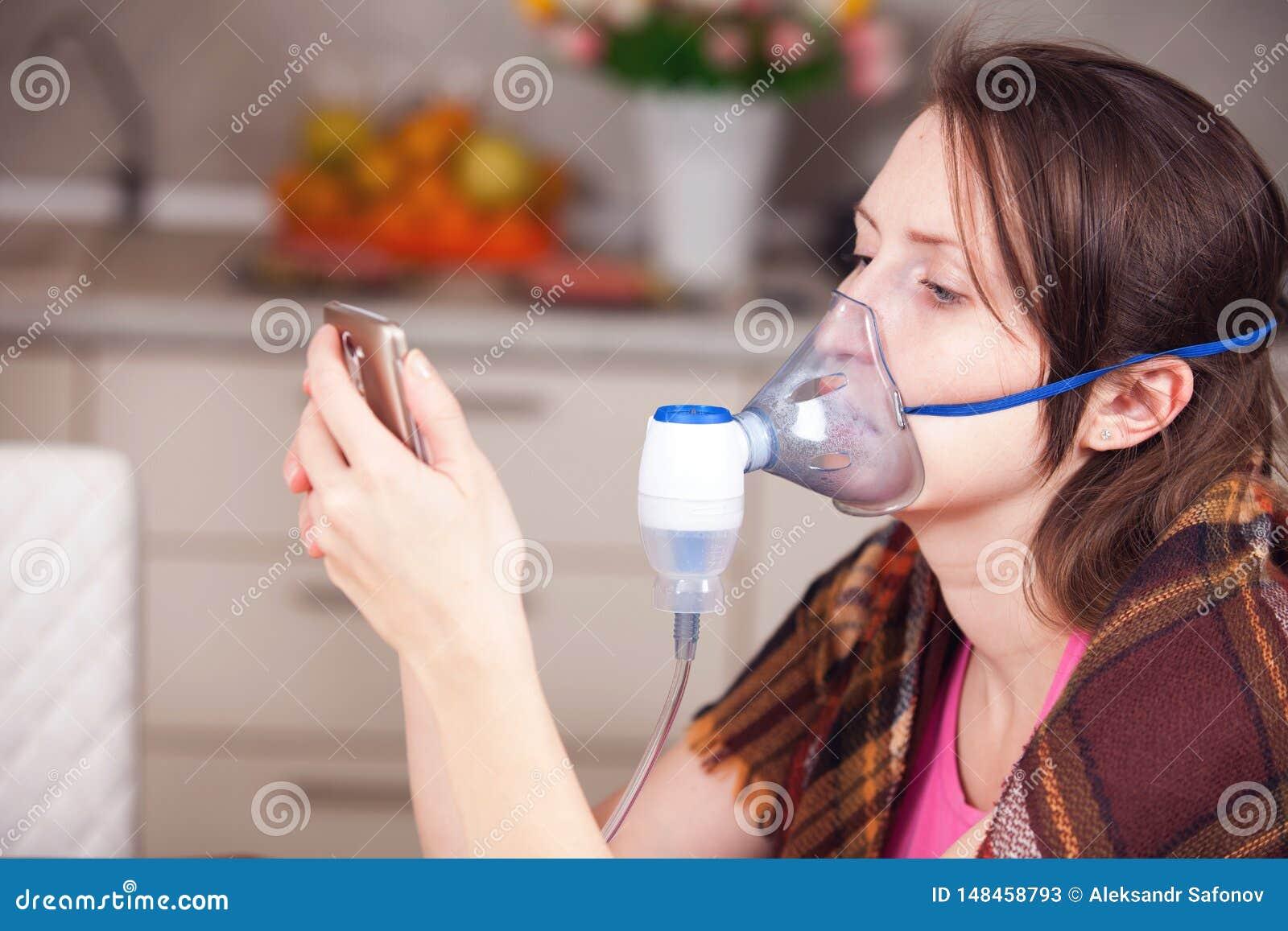 Ung kvinna som hemma g?r inandning med en nebulizer