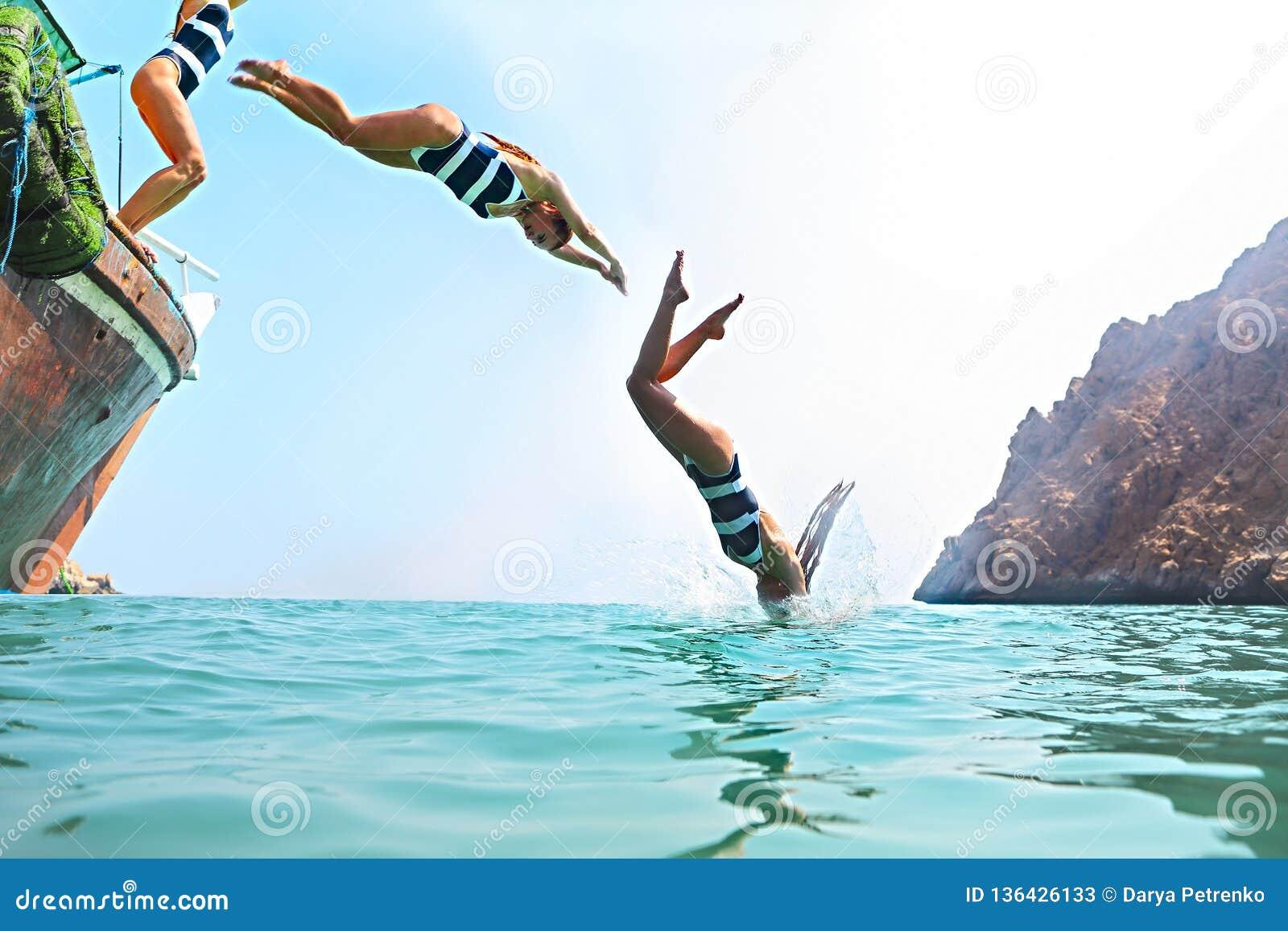Ung kvinna som hoppar från en segelbåt