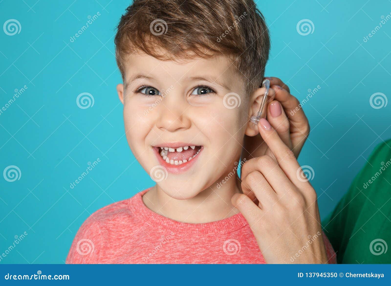 Ung kvinna som justerar liten sons hörapparat på färgbakgrund