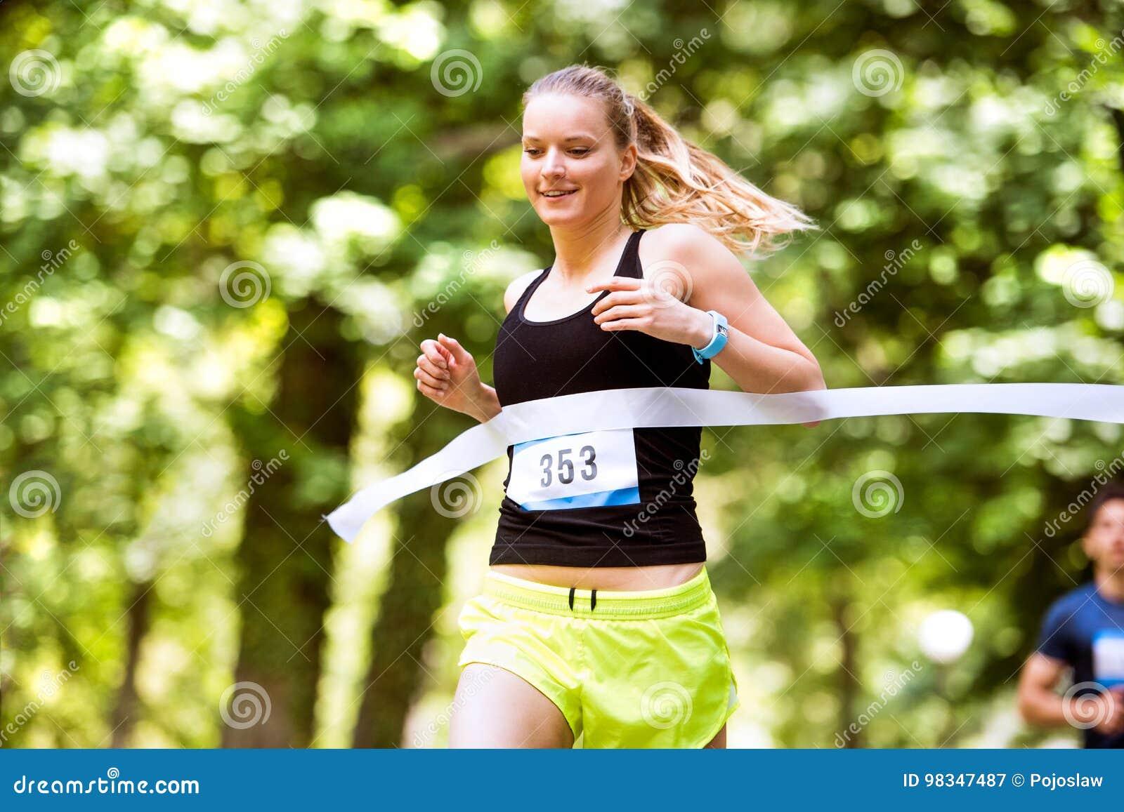 Ung kvinna som kör loppet som korsar mållinjen