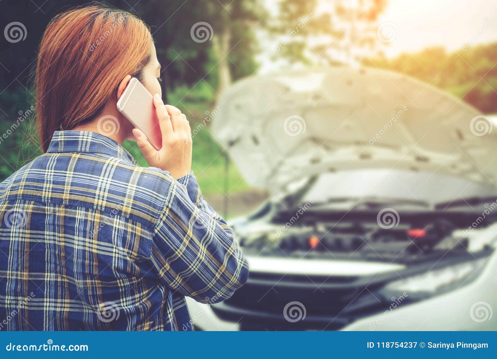 Ung kvinna som kallar för hjälp med hans brutna down för bil vid t