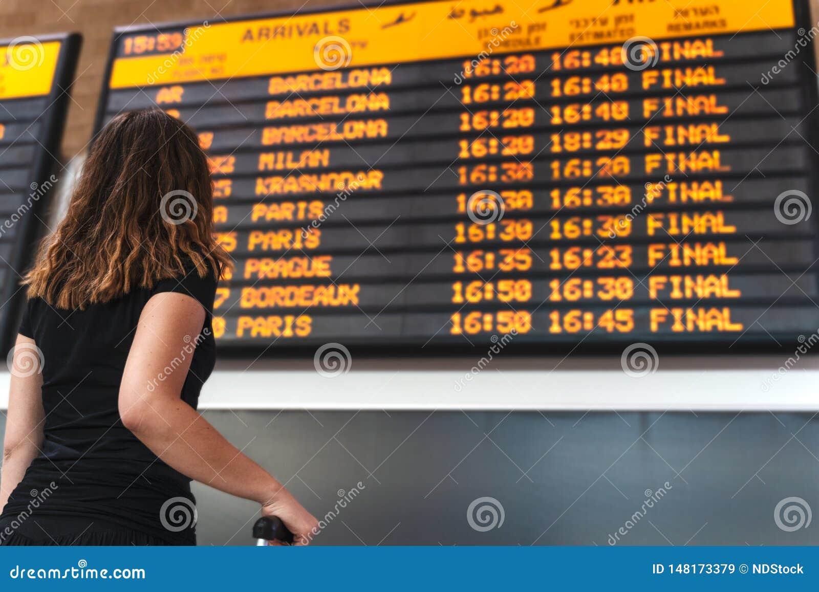 Ung kvinna som kontrollerar schemat på flygplatsen
