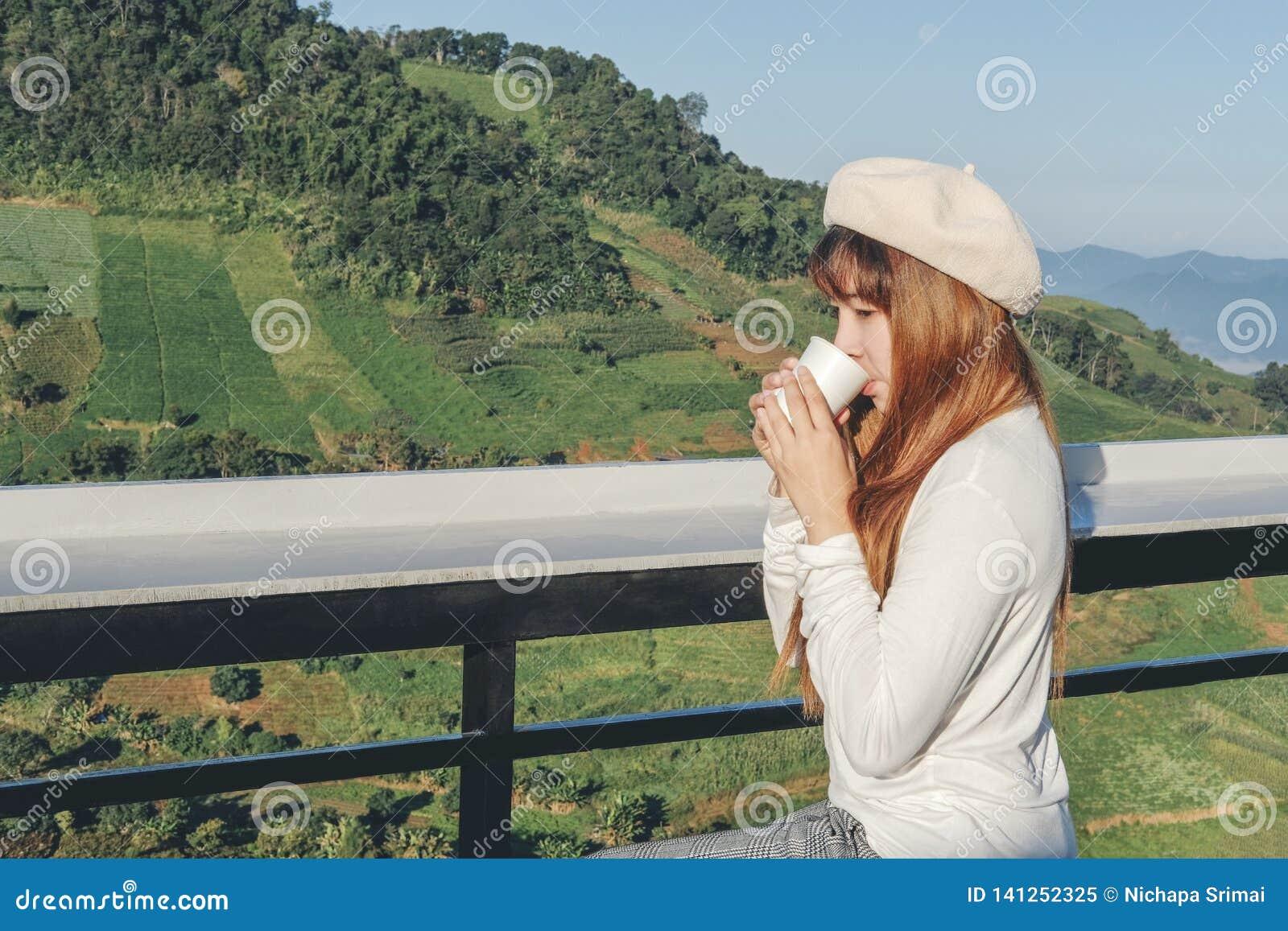 Ung kvinna som kopplar av och dricker kaffe på bergkafét