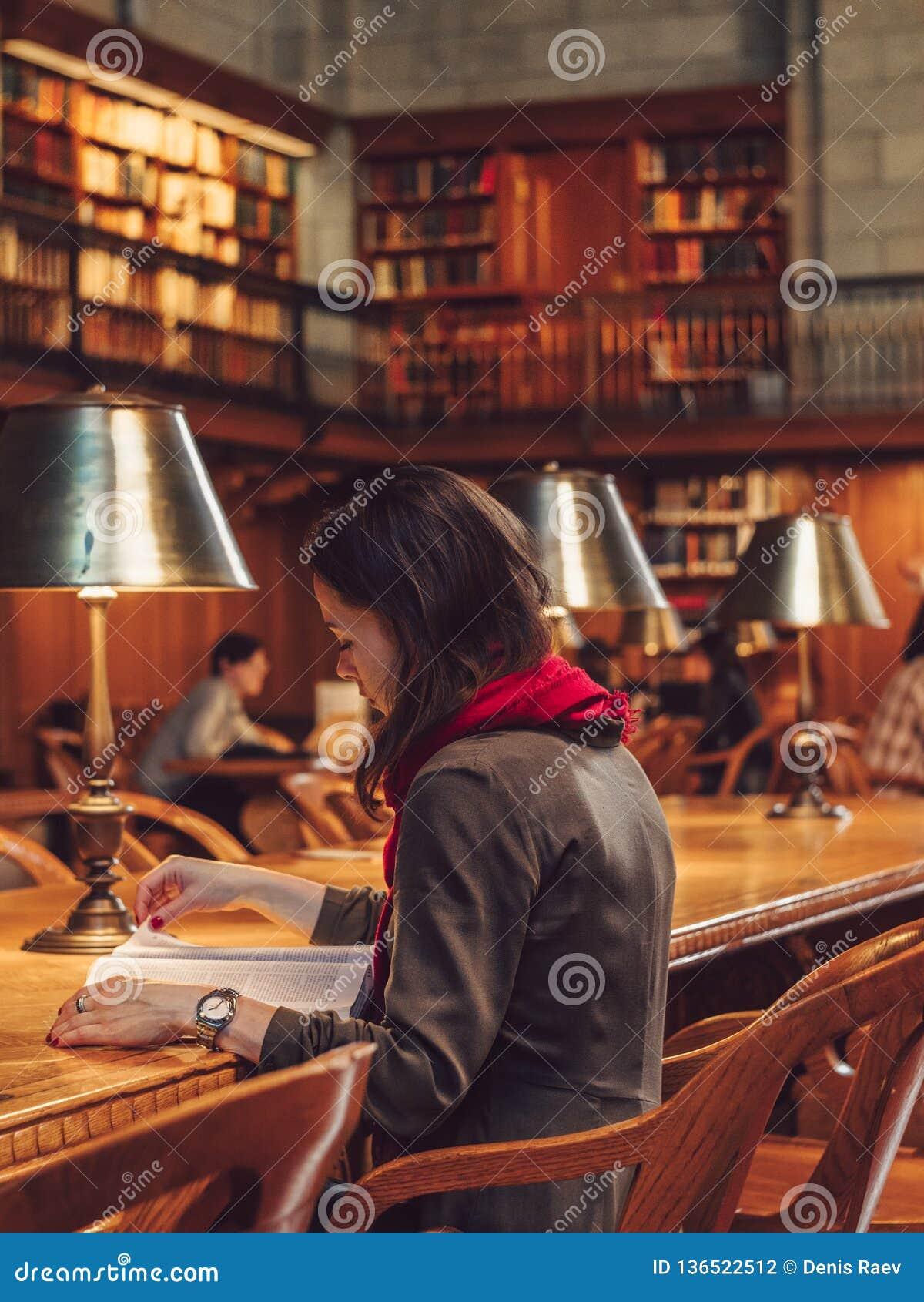 Ung kvinna som läser en bok i arkivet