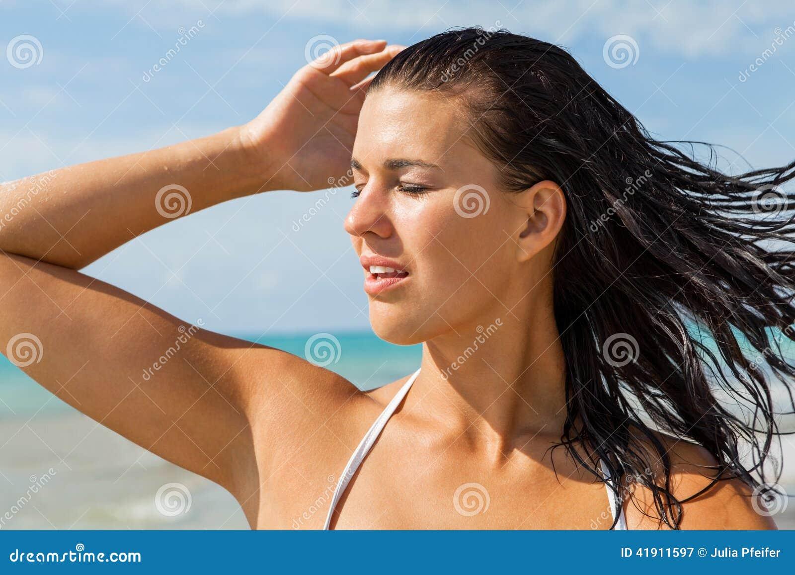 Ung kvinna som långt borta ser i stranden
