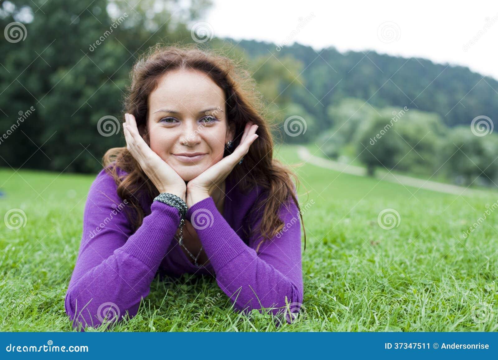 Ung kvinna som ligger på en grön gräsmatta