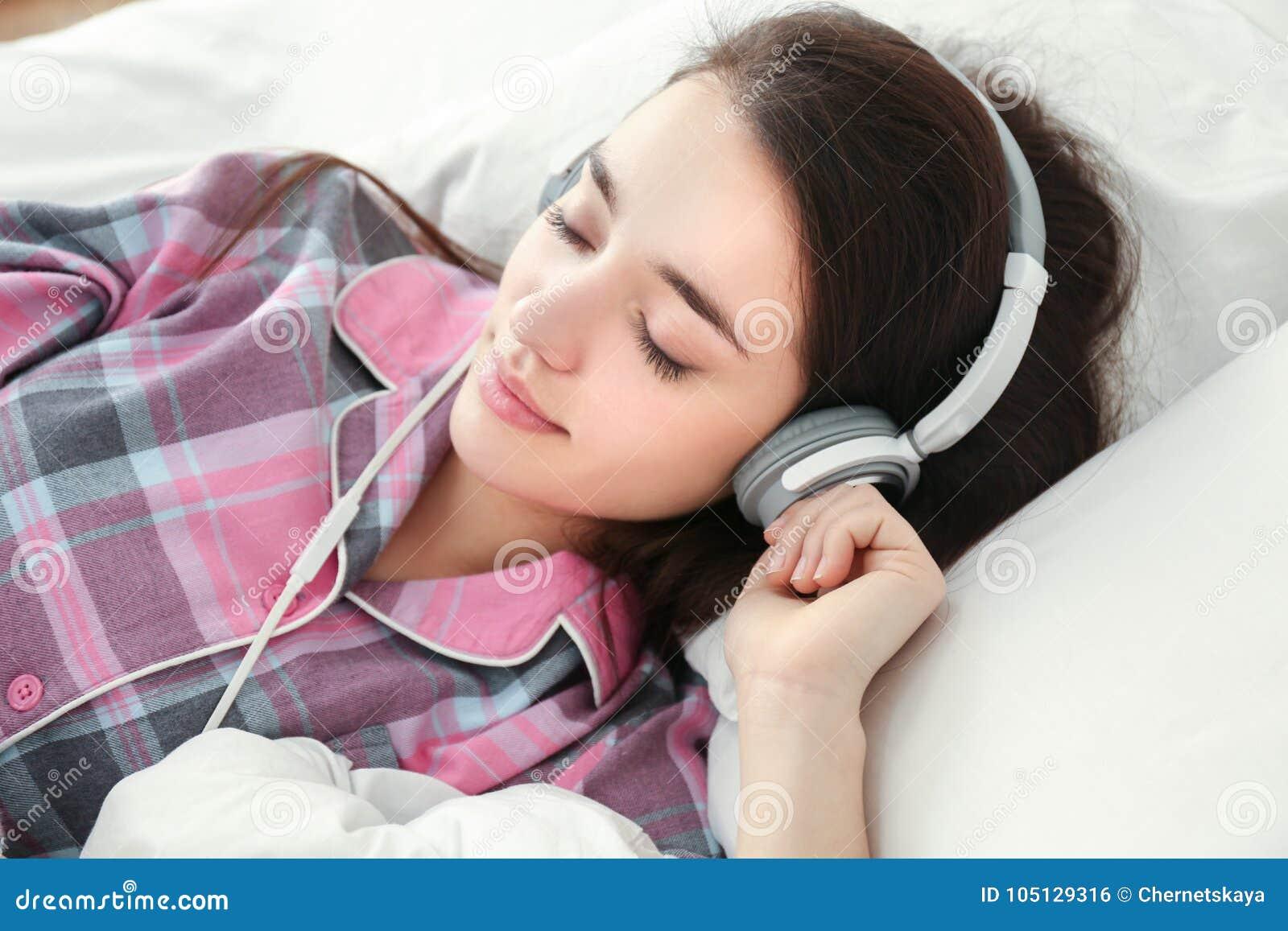 Ung kvinna som lyssnar till musik i hörlurar