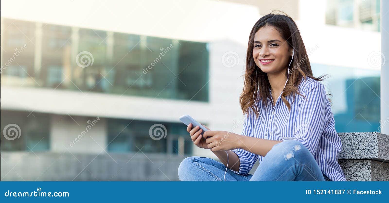 Ung kvinna som lyssnar till musik och ser kameran som är utomhus- med kopieringsutrymme